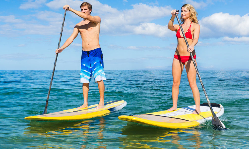 man and woman paddling stand-up paddleboards from their yachts watersports gear collection