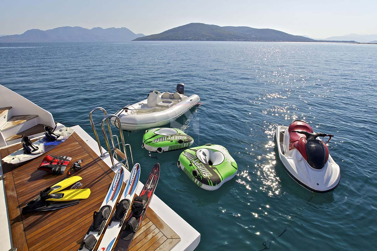 a collection of cool water toys on the deck of and off the back of a luxury yacht