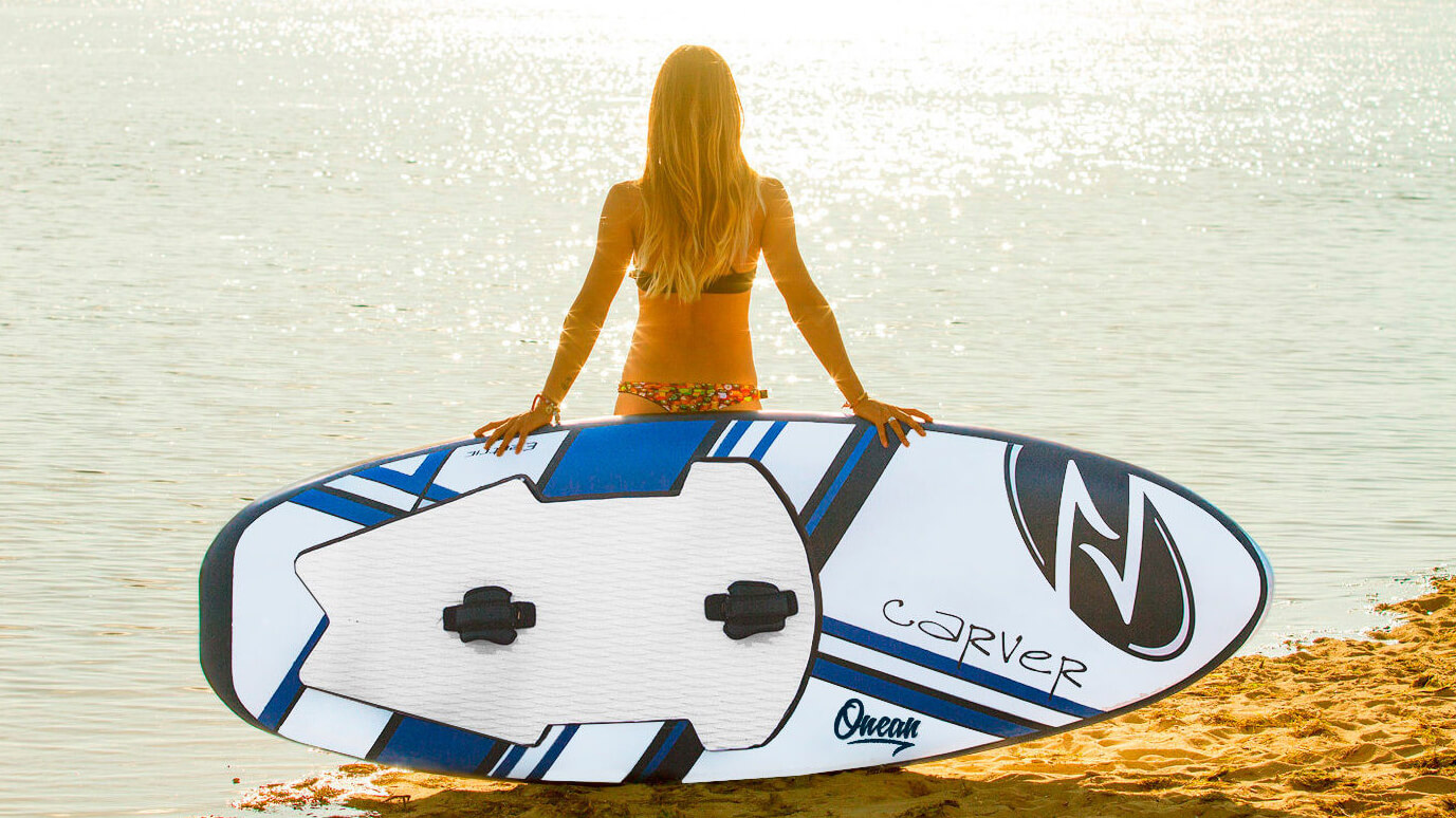 girl on beach with onean electric jet board looking at ocean