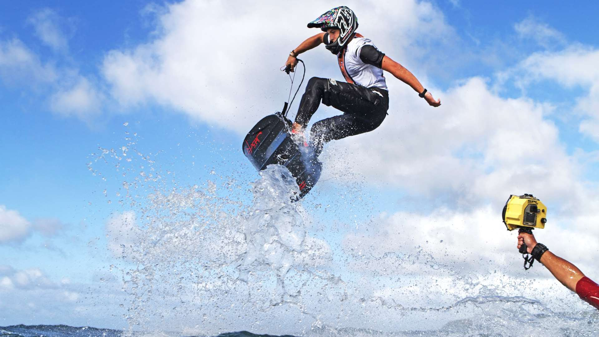 a young man jumping a jet surf very high